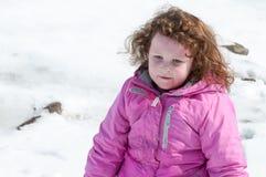 Junges kleines Mädchen, welches das Rodeln draußen an einem Schneetag genießt Stockbilder