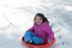Junges kleines Mädchen, welches das Rodeln draußen an einem Schneetag genießt Stockbild