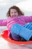 Junges kleines Mädchen, welches das Rodeln draußen an einem Schneetag genießt Stockfotografie