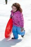 Junges kleines Mädchen, welches das Rodeln draußen an einem Schneetag genießt Stockfoto