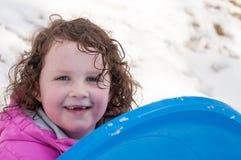 Junges kleines Mädchen, welches das Rodeln draußen an einem Schneetag genießt Lizenzfreie Stockbilder