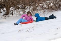 Junges kleines Mädchen, welches das Rodeln draußen an einem Schneetag genießt, während ihr Bruder auf das hintere Schleppen entla Stockbild