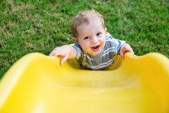 Junges Kleinkindjungenkind, das auf Dia spielt Stockfoto