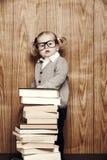 Junges kluges Mädchen mit Büchern und Gläsern Stockbilder