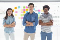 Junges kreatives Team, das an der Kamera lächelt Lizenzfreie Stockfotos