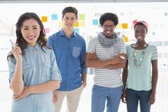 Junges kreatives Team, das an der Kamera lächelt Lizenzfreie Stockfotografie