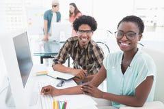 Junges kreatives Team, das am Schreibtisch arbeitet Lizenzfreie Stockbilder