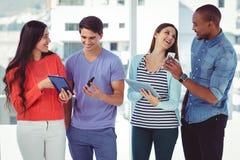 Junges kreatives Team, das Telefone und Tabletten betrachtet stockfotos