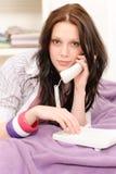 Junges Kursteilnehmermädchen, das über das Telefonlügen spricht Lizenzfreie Stockfotografie