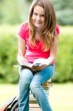 Junges Kursteilnehmermädchen, das auf Stapel der Bücher sitzt Stockfoto