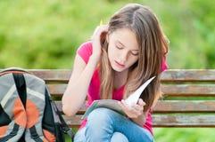 Junges Kursteilnehmermädchen, das auf Bank sitzt Lizenzfreie Stockbilder