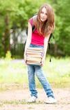Junges Kursteilnehmermädchen, das großen Stapel der schweren Bücher anhält Stockfoto