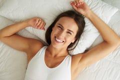 Junges lächelndes Frauengefühl entspannte sich und ruhig, nachdem es geweckt hatte lizenzfreie stockfotografie
