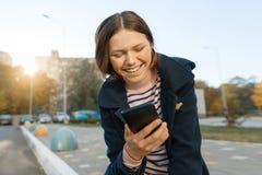 Junges lächelndes jugendlich Mädchen mit Handy, sonniger Herbsttag, Mädchen im Mantel, goldene Stunde stockfotografie