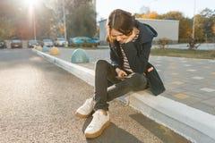 Junges lächelndes jugendlich Mädchen mit Handy, sonniger Herbsttag, Mädchen im Mantel, goldene Stunde lizenzfreie stockfotos