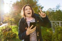Junges lächelndes jugendlich Mädchen zeigt sich Zeigefinger, Aufmerksamkeitsidee Eureka, Hintergrund im Freien, goldene Stunde lizenzfreie stockbilder
