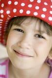 Junges lächelndes Mädchen acht Jahre alt im Großen roten pana Lizenzfreies Stockbild