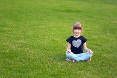 Junges lächelndes Mädchen, das auf einem Gras sitzt Stockfoto