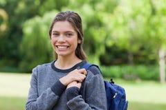 Junges lächelndes Mädchen, das in einem Park aufrecht steht Lizenzfreie Stockfotos