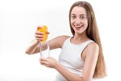 Junges lächelndes Mädchen, das Saft von der Orange bedrängt lizenzfreie stockbilder