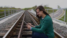 Junges lächelndes Mädchen, das Tablette und Stellung an der Eisenbahn verwendet Tragende Gläser und angekleidet im Grün stock video footage