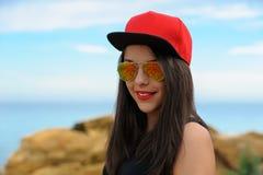 Junges lächelndes Mädchen in der roten Kappe Stockfotos