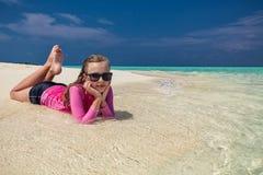 Junges lächelndes Mädchen mit der Sonnenbrille, die auf tropischen Strand legt lizenzfreie stockfotos