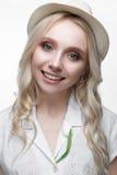 Junges lächelndes Mädchen mit Locken in einem Hut Ein schönes Modell in einem weißen Hemd und in einer Broscheblume Lizenzfreies Stockbild
