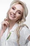 Junges lächelndes Mädchen mit Locken in einem Hut Ein schönes Modell in einem weißen Hemd und in einer Broscheblume Lizenzfreies Stockfoto