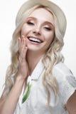 Junges lächelndes Mädchen mit Locken in einem Hut Ein schönes Modell in einem weißen Hemd und in einer Broscheblume Stockfoto
