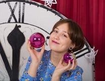 Junges lächelndes Mädchen mit Spielwaren Glaskugeln auf dem Hintergrund der Uhr des neuen Jahres lizenzfreie stockbilder