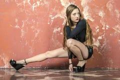 Junges langhaariges langbeiniges dünnes Mädchen in einer schwarzen Strickjacke und in der Lederhose und in den Plattformsandalen Stockbilder