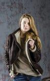Junges langhaariges Mädchen in einer Lederjacke mit Pelzkragen und -jeans Stockfoto