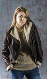 Junges langhaariges Mädchen in einer Lederjacke mit Pelzkragen und -jeans Lizenzfreie Stockfotografie