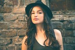 Junges Latinofrauenporträt mit Hut in vorderem altem Haussommer d stockfotografie