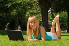 Junges lächelndes Mädchen auf dem Gras mit Laptop Stockfotografie