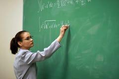 Junges Lehrerschreiben auf dem Vorstand lizenzfreies stockfoto