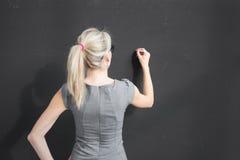 Junges Lehrerschreiben mit weißer Kreide auf leerer Tafel im Klassenzimmer lizenzfreie stockfotos