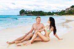 Junges liebevolles glückliches Paar auf dem tropischen Strand, sitzend auf Sand Stockbild
