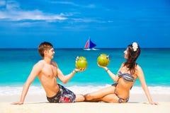 Junges liebevolles glückliches Paar auf tropischem Strand, mit Kokosnüssen Stockbilder