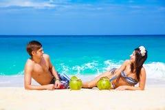 Junges liebevolles glückliches Paar auf tropischem Strand, mit Kokosnüssen Stockfoto