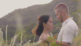 Junges Liebhaberhändchenhalten und Schauen zu den Augen auf tropischer Berglandschaft Mann und Frau, die Hände und das Küssen ber stock video footage