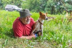 Junges liegender Basenji und sein älterer Meister ein Hinterhalt Lizenzfreies Stockfoto