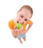 Junges lustiges Mädchen essen Apfel Lizenzfreie Stockbilder