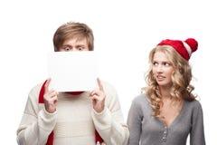 Junges lustiges Weihnachtspaar-Holdingzeichen Lizenzfreie Stockfotografie