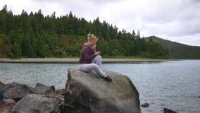 Junges Mädchen, das in der Natur sitzt und in der Hand mit einem Smartphone lacht stock video