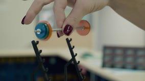 Junges Mädchen, athletisch, in der Turnhalle Sie hebt ein kleines Barbellmodell, mit zwei Fingern an Nahaufnahme stock video