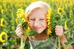 Junges Mädchen auf dem Gebiet, das mit Sonnenblumen spielt Lizenzfreie Stockbilder