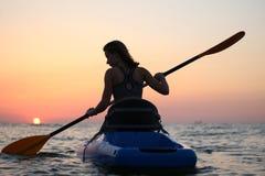 Junges Mädchen auf dem Kajak grüßt die Dämmerung der Sonne stockfotografie
