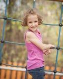 Junges Mädchen auf dem kletternden Netz, das an Gesichtskamera sich wendet Lizenzfreie Stockbilder